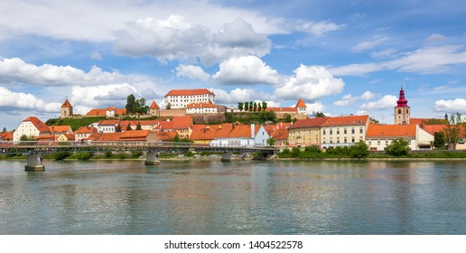 Old city of Ptuj, Slovenia - panoramic view from Drava river. Castle Ptuj on hill above red buildings of oldest town in Slovenia
