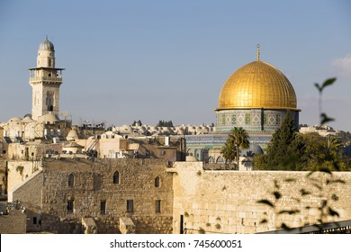 Old city quarter of ancient Jerusalem with light brown stone walls of houses, high tower and dome of the mosque against the blue sky