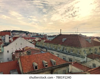 Old city as seen from above roofs of buildings in some town. Architecture from aerial view and beautiful sunset sky. Scenery of houses and constructions. Urban exploration. Lisbon Portugal style.