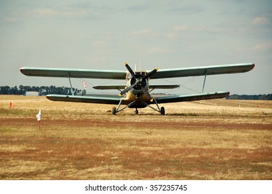 Old classic Antonov (AN-2) cornhusker airplane on the field.