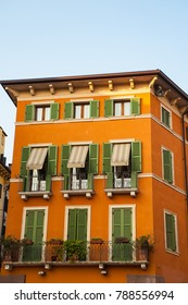 Old, classic apartment building painted orange, in Verona, Italy