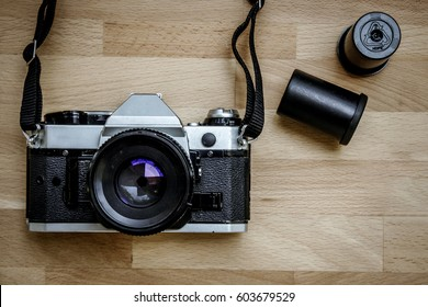 Old Classic Camera With Film Roll On Wooden Background.