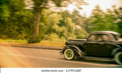 Old classic car driving fast on a vintage car rally blurred background and the car is out of focus