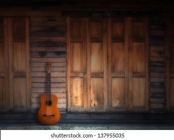 old classic guitar on Texture of old Wood Door and Wall Front Home