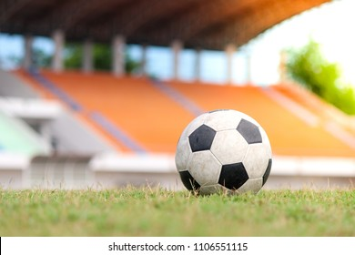 Old and classic soccer ball or football ball on green field with blurred stadium background. Soccer or football concept.
