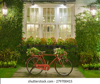 old classic style vintage red bicycle with white window and garden background