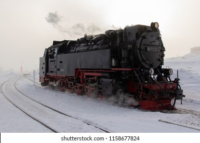 Old classical black and red vintage steam locomotive at the foggy snowy top of the Brocken mountain in Harz, Saxony-Anhalt, Germany. Winter wonderland.