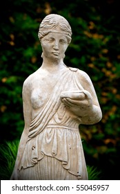 An old, classical style stone statue of a young woman holding a book.