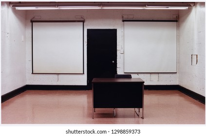 Old classroom with movie screens and desk.