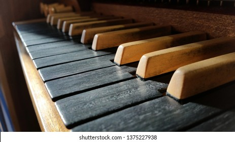 Old classy wooden musical instrument keyboard closeup, pipe organ manual, keys macro, dramatic high contrast lighting. Classical music concert or church sacral music concept