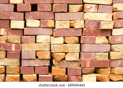Old clay bricks stacked in the wall as a background.