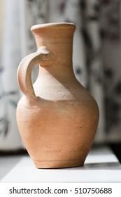 Old clay ceramic vase next to window still life
