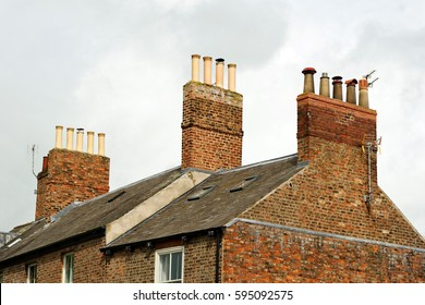 Old clay chimney pots and brick chimney stacks on old tiled roof complete with TV aerials in England, UK.