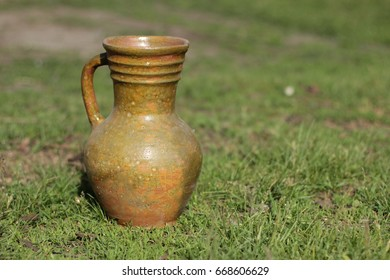 Old clay jug for water or wine on a background of green gras. Old greybeard of the last century on a green backgroun.