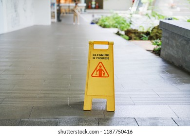 old cleaning in progress warning sign with blurred worker mopping floor