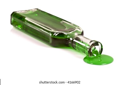 Old clear glass medicine bottle laying on it's side spilling a thick green liquid from the opening.  Isolated on white.