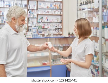 Old client of drugstore consulting with pharmacist about medicines. Female specialist helping, giving white pill bottle and instructing. Pensioner with grey hair wearing in white t shirt.