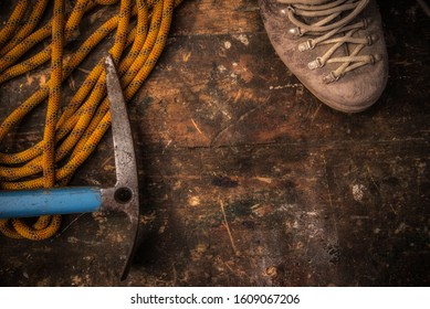 Old climbing equipment on vintage wooden table, top view: rope, clamp, ice axe, shoes