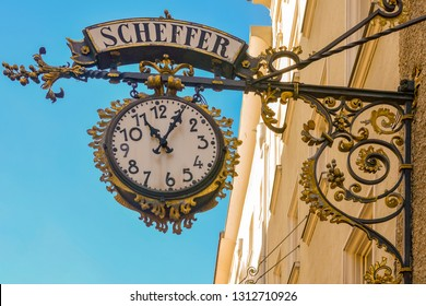 Old Clock is hanging on wall of house on famous historical street Getreidegasse in Salzburg. Salzburg is on banks of River Salzach, at northern boundary of Alps. Salzburg, Austria. Scheffer street