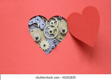 Old clock mechanism inside open heart cutting from red paper