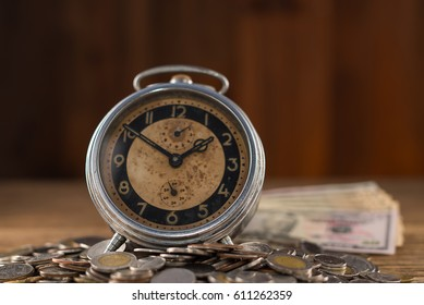 old clock and money on wood background business concept