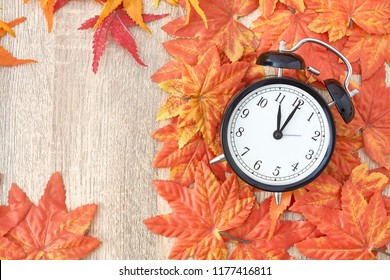 Old clock on autumn leaves on wooden table on natural background, day noon light Blank Space for text