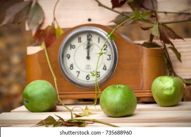 An old clock on a park bench, autumn leaves and apples next to them. The dial of the antique clock. Style vintage