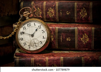 Old clock over books still life in Low-key, copy space. Concept of time,the past or deadline.