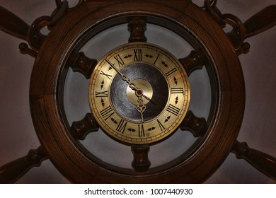 Old clock in shape of a ship wheel