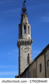 Old clock tower against a blue sky in Avignon, France