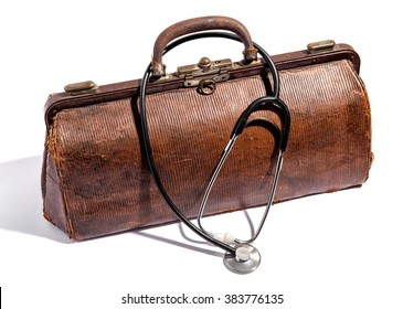 Old closed battered brown leather doctors bag for instruments and equipment with a stethoscope draped over the top on white