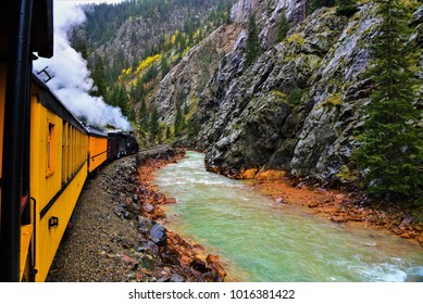 Old coal fired steam engine travels south along the narrow gauge railroad near Silverton, CO.  The Animas River creates a beautiful contrast with the train and black rock canyon.