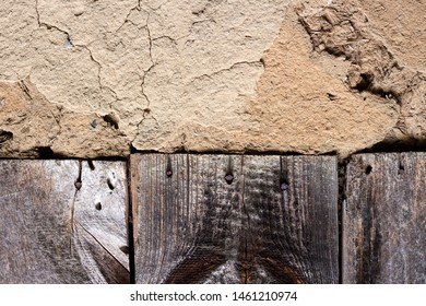 Old cob wall with cracked surface and old wooden boards. Vintage background for design purposes
