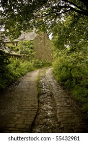 An old cobbled road leading to a small cottage.