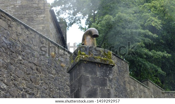 Old cobblestone wall with chimney vent.