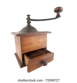Old coffee grinder with ground coffee in the drawer