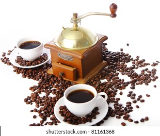 Old coffee grinder and roasted coffee beans over white background