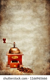 an old coffee grindger with coffee beans over old grunge vintage rustic brown background with copy space