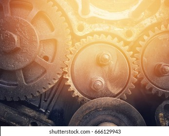 The old cogwheels join together background with sun flare effect.