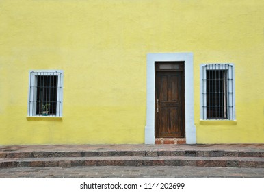 Old Colonial house traditional solid oak wooden door and windows with handcrafted iron grilles on a soft yellow stucco wall, in Santiago de Querétaro Mexico.
