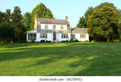 An old Colonial house in Yorktown VA from the late 1800's early 1900's with a large front lawn of lush green grass.