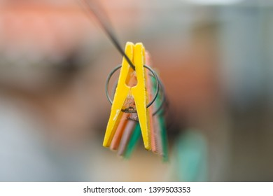 old colored clothespins hanging on a wire for drying clothes. Clothespins on blurred background