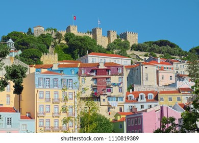 Old colored Portuguese houses on a hillside with St. George Castle at the top, located in the city of Lisbon, Portugal.