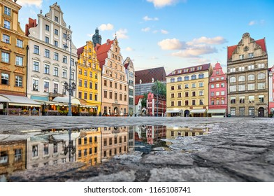 Old colorful buildings reflecting in a puddle on Rynek square in Wroclaw, Poland