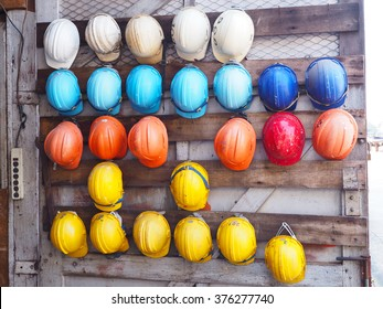 old colorful construction helmets hang on wooden background