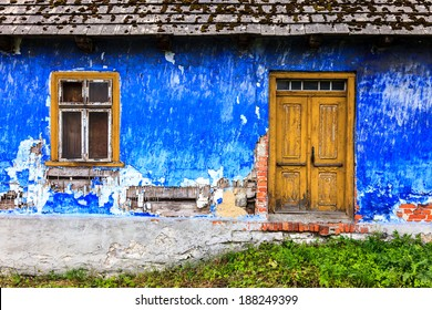 old colorful house front facade with door and window, pained wall and roof