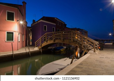 Old colorful houses and boats at night in Burano, Venice Italy.