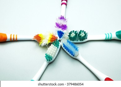 Old colorful toothbrushes on gray background.