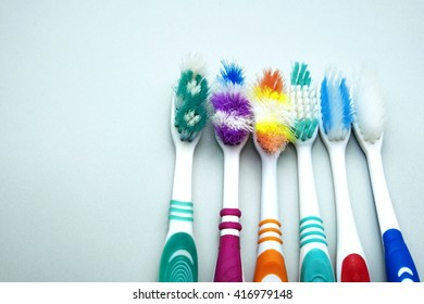 Old colorful toothbrushes on gray background. Space for texts.