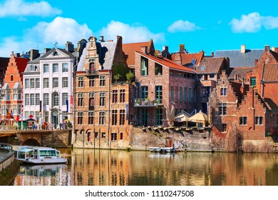 old colorful traditional houses along the canal and boats in popular touristic destination Ghent, Belgium
